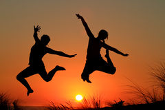 Sunset jump sisters Stock Photography
