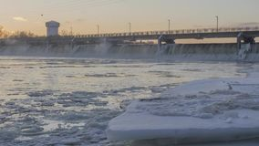 A Winter Shot of the Coon Rapids Dam and Brooklyn Park Water Tower over an Icy Mississippi River at Sunset 4K Timelapse stock footage
