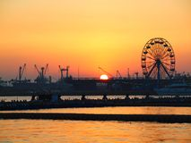 Sunset at Kaohsiung Port. Cranes and a Ferris wheel at Kaohsiung harbor at sunset Stock Photos