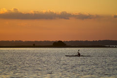 Sunset kayaking. Man in kayak sailing in sunset Stock Photos
