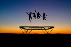 Sunset kids on trampoline. Silhouette of kids on trampoline in sunset stock photo