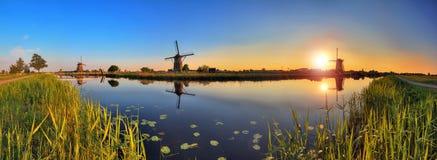 180 sunset Kinderdijk. Beautiful panoramic image of the dutch windmills at Kinderdijk, the Netherlands. An UNESCO world heritage site Stock Images