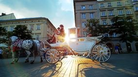 Sunset in Krakow city center, Poland. KRAKOW, POLAND - JUNE 12, 2018: Enjoy the sunset from Main Market square with a view on riding horse-drawn carriage, that stock video footage