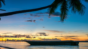 Sunset on Kri Island. Boats under Palmtrees. Raja Ampat, Indonesia, West Papua. Sunset on Kri Island. Boats under Palmtrees. Raja Ampat, Indonesia. West Papua royalty free stock photo