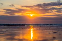 Sunset on the Kuta beach with reflection in the water on the isl. And of Bali Stock Photo