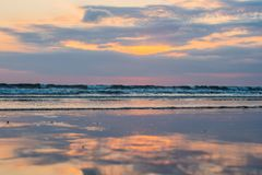 Sunset on the Kuta beach with reflection in the water on the island of Bali royalty free stock image