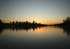 Sunset at Lago Igapo lake localized in Londrina city. Londrina, Brazil - July 24, 2017: Sunset at Lago Igapo lake localized in Londrina city. The city silhouette Stock Photos
