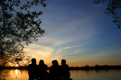 Sunset at the lake. Group of firends sitting watching the sunset at the lake Stock Images