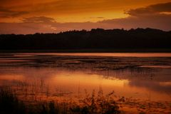 Sunset at the Lake. Orange Light Covers Sky and the Lake Surface. Horizontal Photography. Chain O'Lakes, Illinois, USA Stock Image