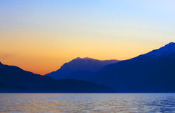 Sunset on the lake. Sunset behind the mountains on the lakeside Stock Photo