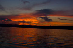 Sunset on the lake. Summer, red and orange clouds, reflections in water Royalty Free Stock Images