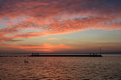Sunset at Lake Balaton. Sunset with a swan in the foreground and people on a pier at Lake Balaton, Hungary Royalty Free Stock Image