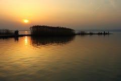 Sunset at Lake Balaton. Sunset with people on bicycles and fishing on a pier at Lake Balaton, Hungary stock photo