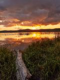 Sunset by the lake. Beautiful sunset on lake with colorful clouds and Reflexion on lake. Log wood in the foreground royalty free stock images