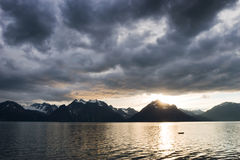 Sunset at lake with dark clouds stock photos