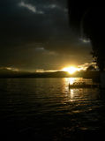Sunset on the lake in dark cloudy evening. Sunset on the lake with dark cloudy evening, with pier, in Ecuador, South America royalty free stock photos