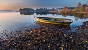Sunset lake with fisherman boat landscape. Stock Photos