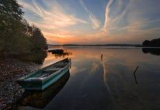 Sunset lake with fisherman boat landscape. Stock Photo