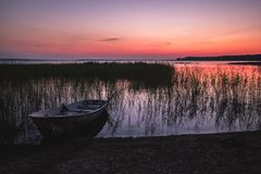 Sunset on the lake, fishing boat on the shore stock photo