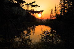 The sunset on the lake `Forest Tale` in the Khamar-Daban. Evening landscape passing day with the setting behind the mountain the sun over the mountain lake Stock Photo