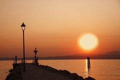 Sunset at lake of Garda with man silouette. A 3:2 landscape sunset at lake of garda with a man siluette near the boat' s docking that seem looking this special Stock Photography