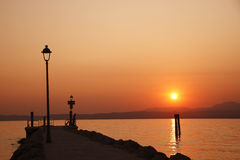 Sunset at lake of Garda with man siluette. A 3:2 landscape sunset at lake of garda with a man siluette near the boat' s docking that seem looking this special Royalty Free Stock Photos