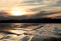 Sunset on lake Hovsgol. Drifting over the peaks and into the clouds the sun over the water surface of Mongolian lakes, a little anxious last boat Stock Photo