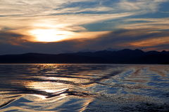 Sunset on lake Hovsgol. Over the Mongolian lake observed the sunset reflected in the water and in the water track from the passage to pleasure catamaran Stock Images