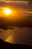 Sunset on the lake. Landscape of sunset on the lake with the sun between the mountains Royalty Free Stock Image