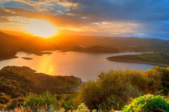 Sunset on the lake. Landscape of sunset on the lake with the sun between the mountains Royalty Free Stock Photography