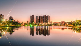 Sunset at a lake of a park with the city on background Royalty Free Stock Photography