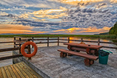 Sunset Lake Pier with Camping Table and Bench Royalty Free Stock Image