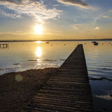 Sunset at the lake. Reflections of light on the flat water of Lake Garda Stock Image