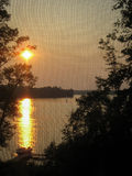 Sunset on Lake through Screen Door Stock Photography