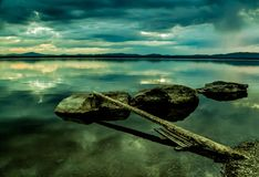 Sunset lake. The shore of the lake with large stones and a lying dry tree Stock Photo