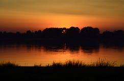 Sunset by a lake. Sunset lake shore wide angel view Stock Photo