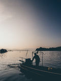 Sunset lake and silhouette of man and motor boat. Royalty Free Stock Image