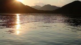 Sunset on Lake Skadar. Montenegro. View from the boat on the water and mountains stock video