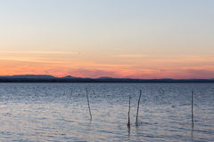Sunset at the lake. With some wooden poles in the water and soft and warm colors in the sky Royalty Free Stock Photo