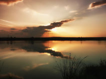Sunset at lake, storm clouds reflected on the surface of the water.  Royalty Free Stock Photos