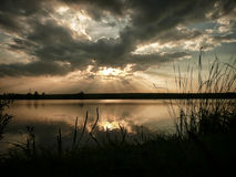 Sunset at lake, storm clouds reflected on the surface of the water royalty free stock photo