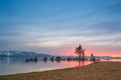 Sunset at Lake Tahoe. With sand beach, mountains covered by snow at background stock images