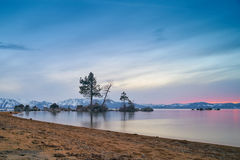 Sunset at Lake Tahoe. With sand beach, mountains covered by snow at background royalty free stock photography