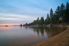 Sunset at Lake Tahoe. With sand beach, mountains covered by snow at background royalty free stock image
