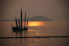 Sunset on lake Tai. Ancient Chinese boat on the golden lake surface stock image