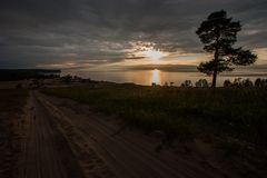 Sunset on the lake with a tree and a sandy road. royalty free stock images