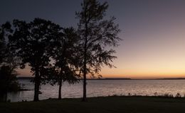 Sunset on the lake, trees in silhouette stock image