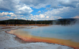 Sunset Lake under overcast cumulus clouds in Black Sand Basin in Yellowstone National Park in Wyoming USA Royalty Free Stock Photography