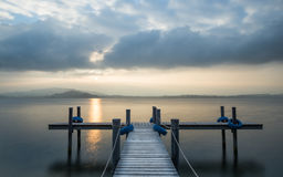 Sunset lake. Wooden pier on the lake. Fog. Long exposure royalty free stock image