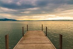 Sunset on lake with wooden pier on overcast day. Zug, Switzerland.  Stock Photography